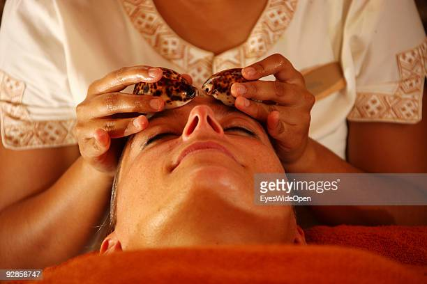 Woman enjoys a Ayurveda health treatment with a Kauri shell in the Chi Spa of in the luxurious ShangriLa's Villingili Resort and Spa Hotel on...