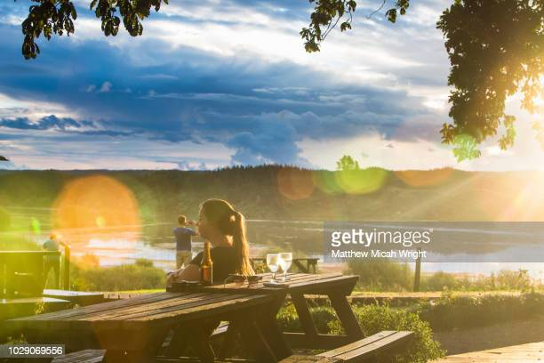 A woman enjoys a beautiful sunset as she sits lakeside along the shore of New Zealand's Lake Aniwhenua.