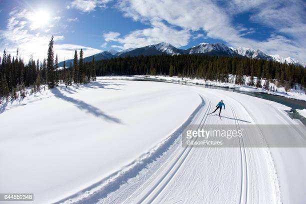 A woman enjoys a cross-country skate ski next to a river in British Columbia, Canada on a sunny day.
