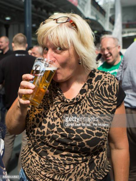 A woman enjoys a pint of beer at the Great British Beer Festival in Olympia London Keningston London organised by the Campaign for Real Ale