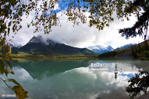 Una mujer disfruta de un viaje de paddleboard en un lago en las montañas rocosas de Canadá, de pie.