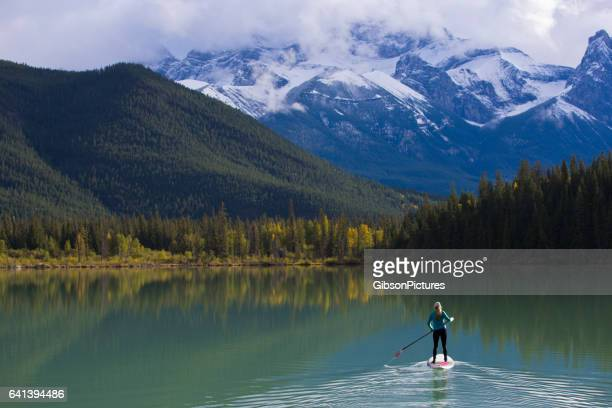 A woman enjoys a stand up paddleboard trip on a lake in the Rocky Mountains of Canada.