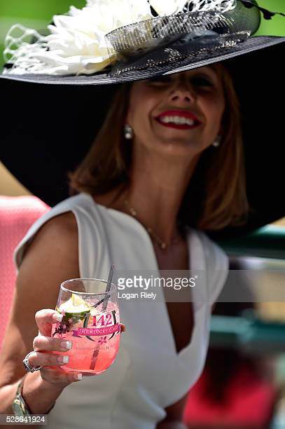 A woman enjoys an Oaks Lily drink prior to the 142nd running of the Kentucky Oaks at Churchill Downs on May 06 2016 in Louisville Kentucky