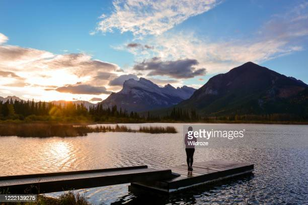 woman enjoys beautiful sunrise with views of mount rundle and vermillion lakes, banff national park - canadian rockies stock pictures, royalty-free photos & images
