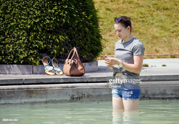 A woman enjoys cooling down in the water of the fountain of the Trocadero next to the Eiffel Tower during the heat wave on June 20 2017 in Paris...