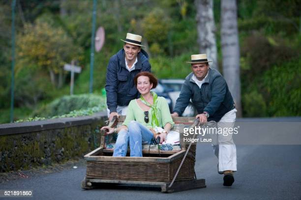 Woman enjoys her ride on the Monte Toboggan Run, Funchal, Madeira, Portugal