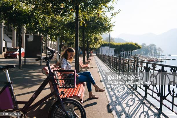 woman enjoys lake promenade with bicycle - スイス ルガーノ ストックフォトと画像