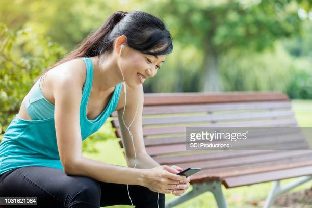 woman enjoys music while taking exercise break in park - chinese music stock pictures, royalty-free photos & images