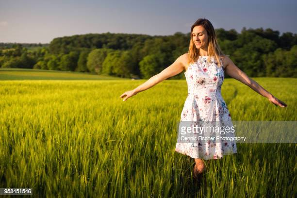 woman enjoys sunset in field - spreading stock pictures, royalty-free photos & images