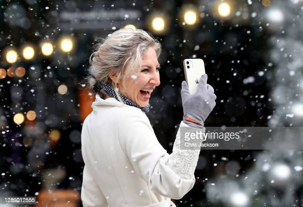 Woman enjoys the artificial snow-fall as Covent Garden welcomes back shoppers and diners after UK lockdown at Covent Garden on December 02, 2020 in...