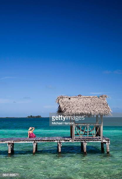 a woman enjoys the crystal clear waters under a wooden dock in belize. - belize stock pictures, royalty-free photos & images