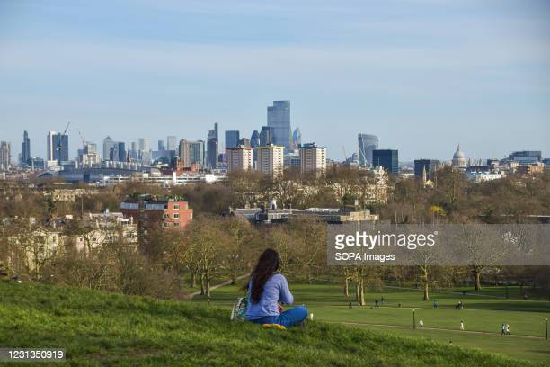 Woman enjoys the view from Primrose Hill in London on a sunny day.