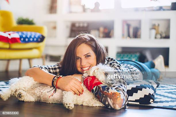 Woman enjoys with small dog on floor