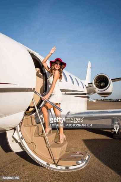 woman entering airplane - first class stock photos and pictures