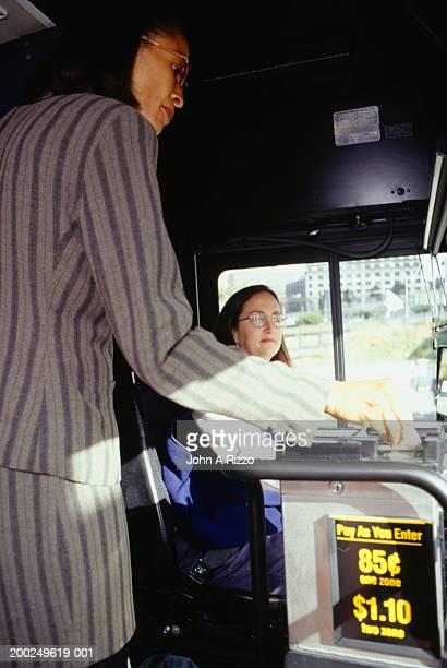 Woman entering bus, paying fare