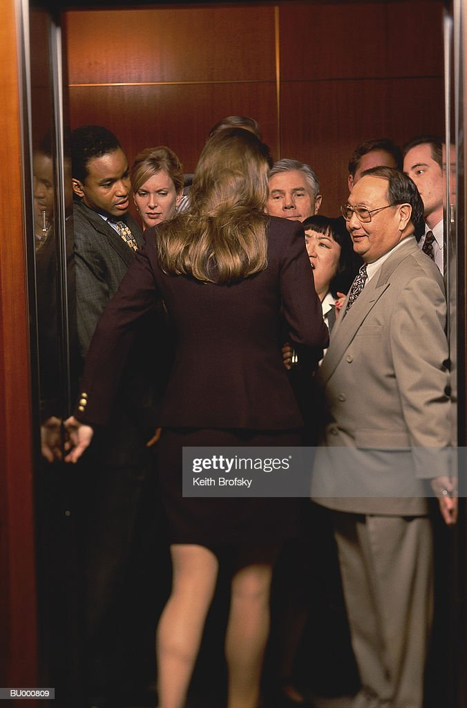 Woman Entering Crowded Elevator : Stock Photo