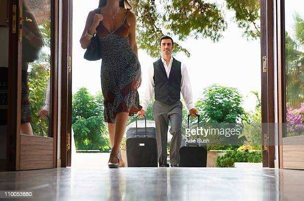 Woman entering hotel man carrying bags