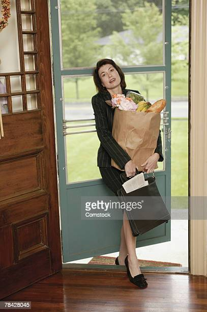 Woman entering house with grocery bag