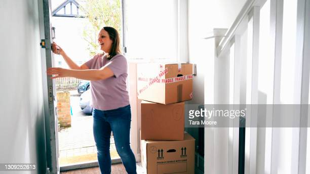 woman entering new house with boxes - entering stock pictures, royalty-free photos & images