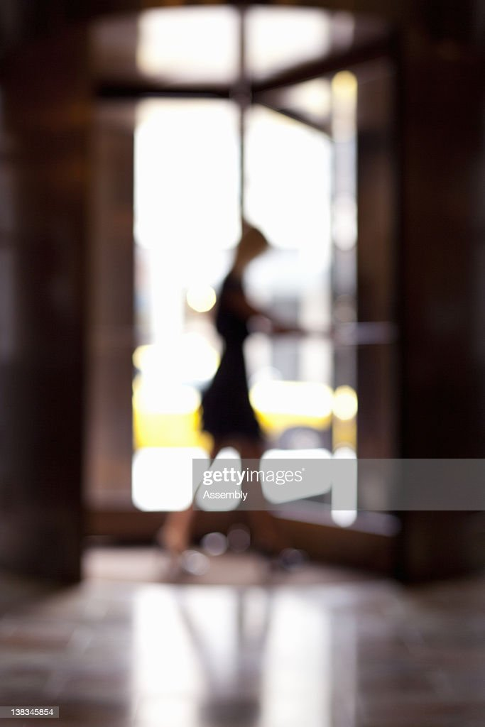 Woman entering revolving door, blur : Stockfoto