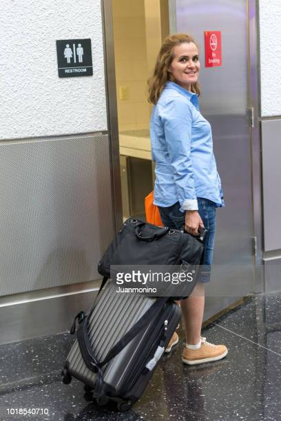 woman entering the airport public restroom - airplane bathroom stock pictures, royalty-free photos & images