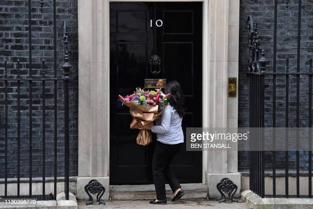 A woman enters 10 Downing Street with a bunch of flowers in London on March 14 ahead of a further Brexit vote British MPs will vote today on whether...