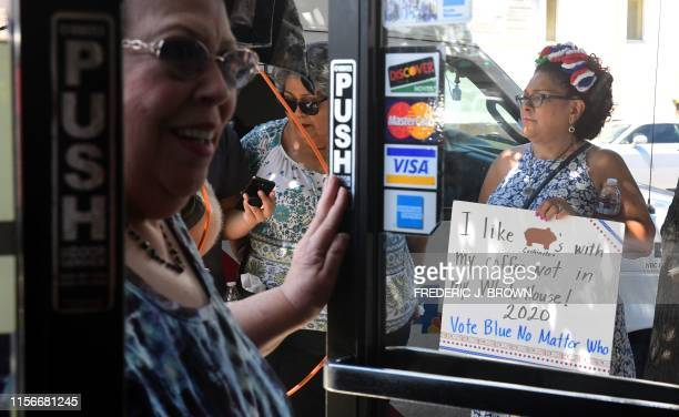 A woman enters a bakery as others outside some holding placards await the arrival of Democratic party candidate Joe Biden who met with patrons at a...