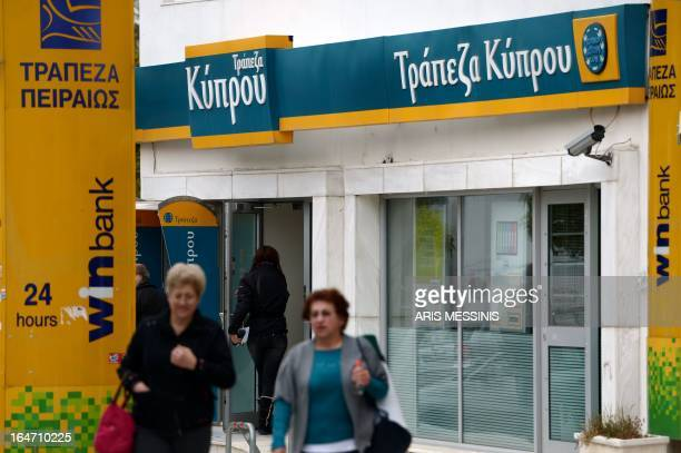 A woman enters a Bank of Cyprus branch in Athens on March 27 as Greek subsidiaries of three Cypriot banks reopened today after Greece's third lender...