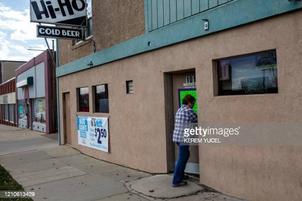 A woman enters a bar amid the coronavirus COVID19 pandemic on April 20 in Sioux Falls South Dakota For months sparsely populated South Dakota watched...