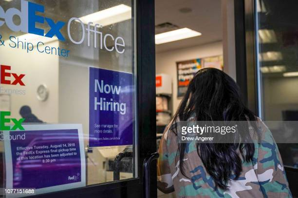 A woman enters a FedEx Office store with 'now hiring' sign on the door in Lower Manhattan January 4 2019 in New York City Following a strong December...