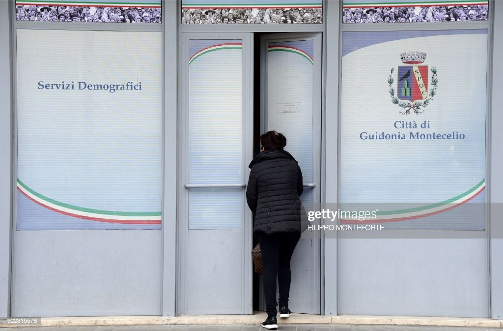 A woman enters a local municipal office in Guidonia on February 1, 2018. In the industrial town of Guidonia near Rome, its first Five Star mayor is pulling out all the stops as the populist movement gears up for a shot at national governance. Tall, bespectacled and originally from France, Michel Barbet won the mayoralty last year amid an outpouring of frustration and anger towards the mainstream political parties. /