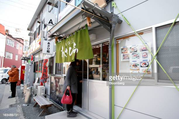A woman enters a sushi restaurant in a temporary shopping area for displaced stores and restaurants in an area damaged by the tsunami following the...