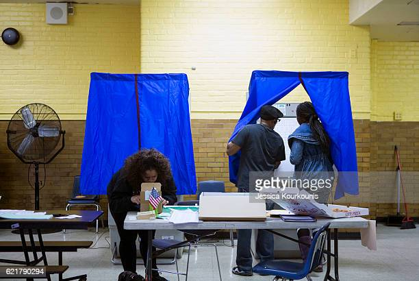 A woman enters a voting booth to cast her vote at Vare Edwin Middle School on November 8 2016 in South Philadelphia Pennsylvania Americans across the...