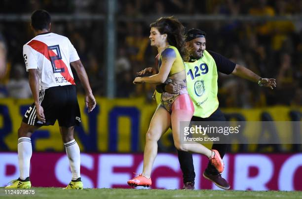 A woman enters the pitch with her body painted with the colors of Rosario Central and Newell's Old Boys as a security official stops her during a...
