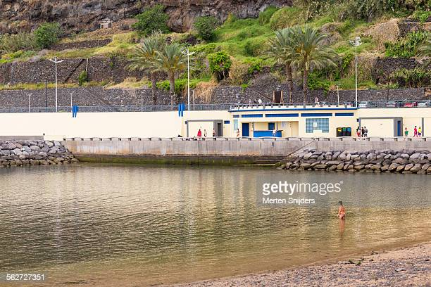 woman enters water at praia da calheta - merten snijders stockfoto's en -beelden