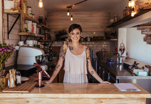 Woman entrepreneur standing at the billing counter of her cafe 940569228