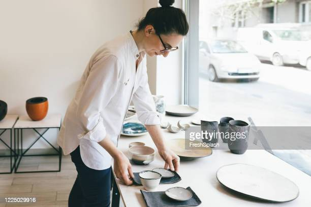 woman entrepreneur working at gallery selling pottery - art dealer stock pictures, royalty-free photos & images