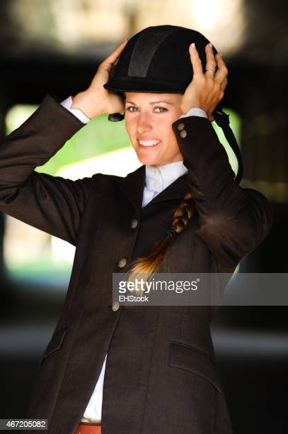 Woman Equestrian Putting On Riding Helmet