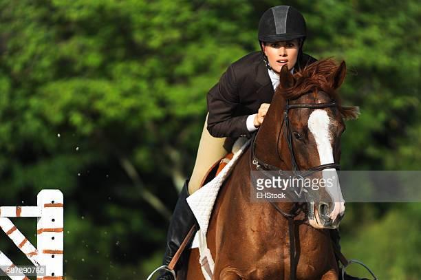 Mujer montando ecuestre en mostrar saltos de caballo