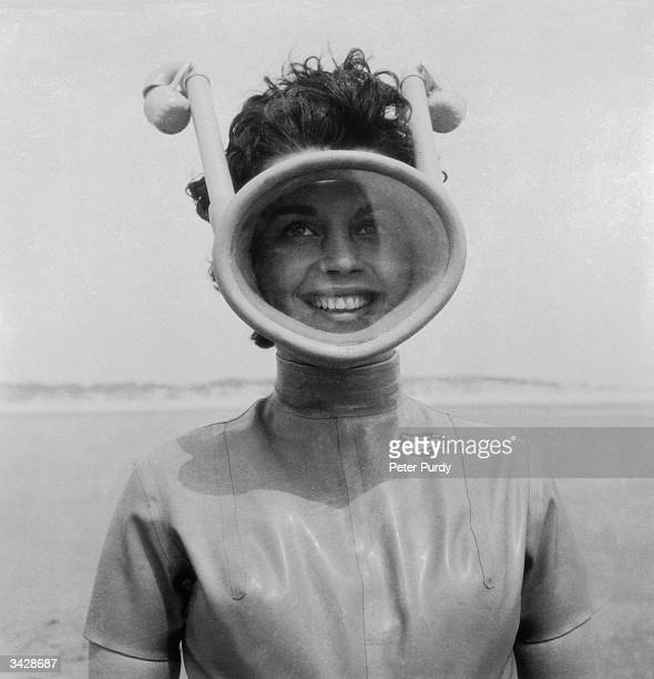 A woman equipped for a diving session with an unusual full face mask with integrated snorkels and wetsuit