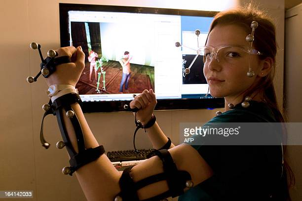 A woman equipped for a fullbody motion capture presents a 3D real time experiment by French logistic systems developer company Dassault Systemes on...