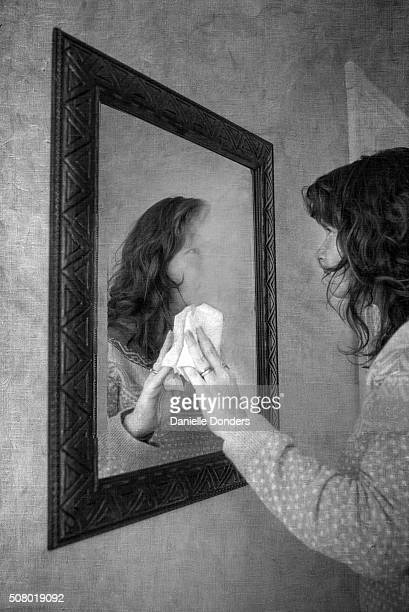 Woman erasing her reflection in a mirror