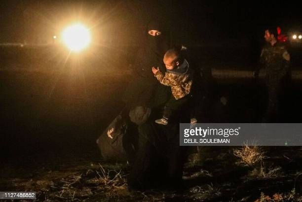 Woman evacuated from the Islamic State group's embattled holdout of Baghouz carries a child as she walks toward a zone held by the USbacked Syrian...