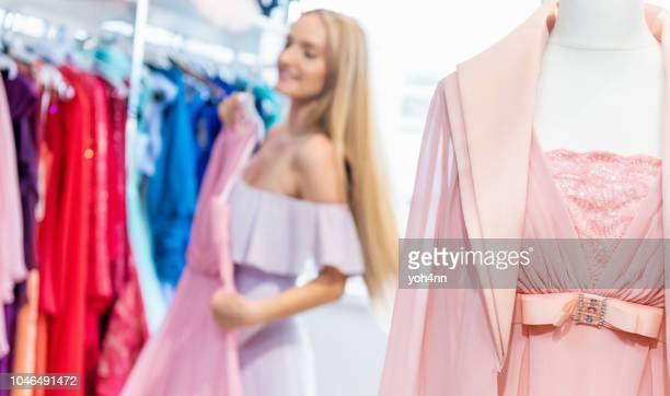woman & evening gowns at clothing store - evening gown stock pictures, royalty-free photos & images