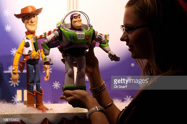 A woman examines a 'Toy Story Collection Buzz Lightyear' and 'Woody' figures at the Toy Retailers Association's annual 'Dream Toys' fair on October...