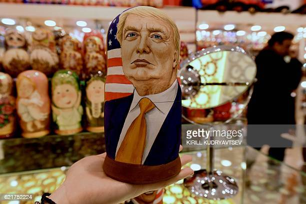A woman examines a traditional Russian wooden nesting doll a Matryoshka doll depicting US Republican presidential nominee Donald Trump at a gift shop...
