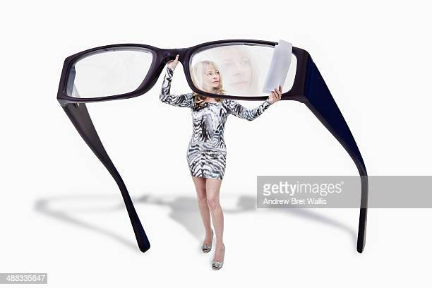 Woman examines document through giant spectacles