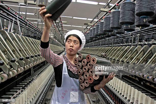 Woman examines yarn at a weaving machine at the Jiangsu Sunshine Co. Ltd. Textile factory at Jiangyin, Jiangsu province, China, on Thursday, April...