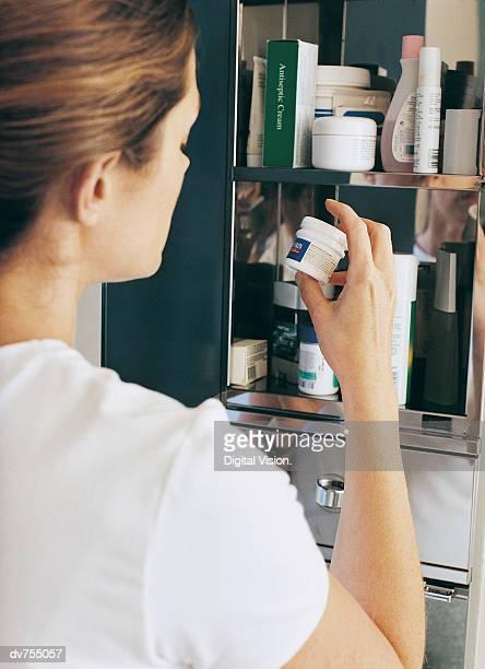 woman examining a bottle of medicine - armoire de toilette photos et images de collection