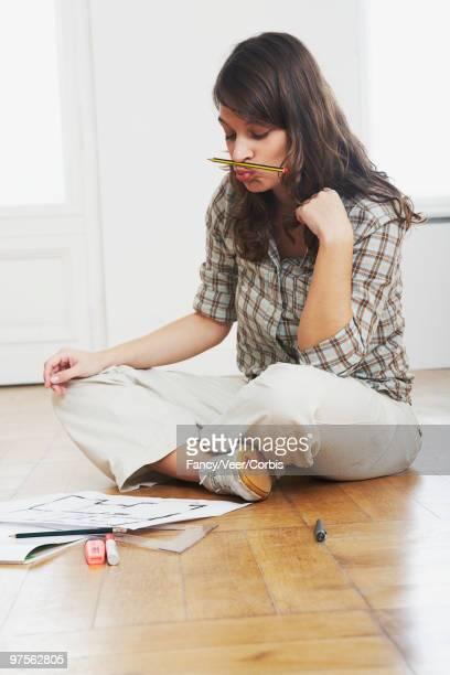 woman examining blueprints - チノパンツ ストックフォトと画像